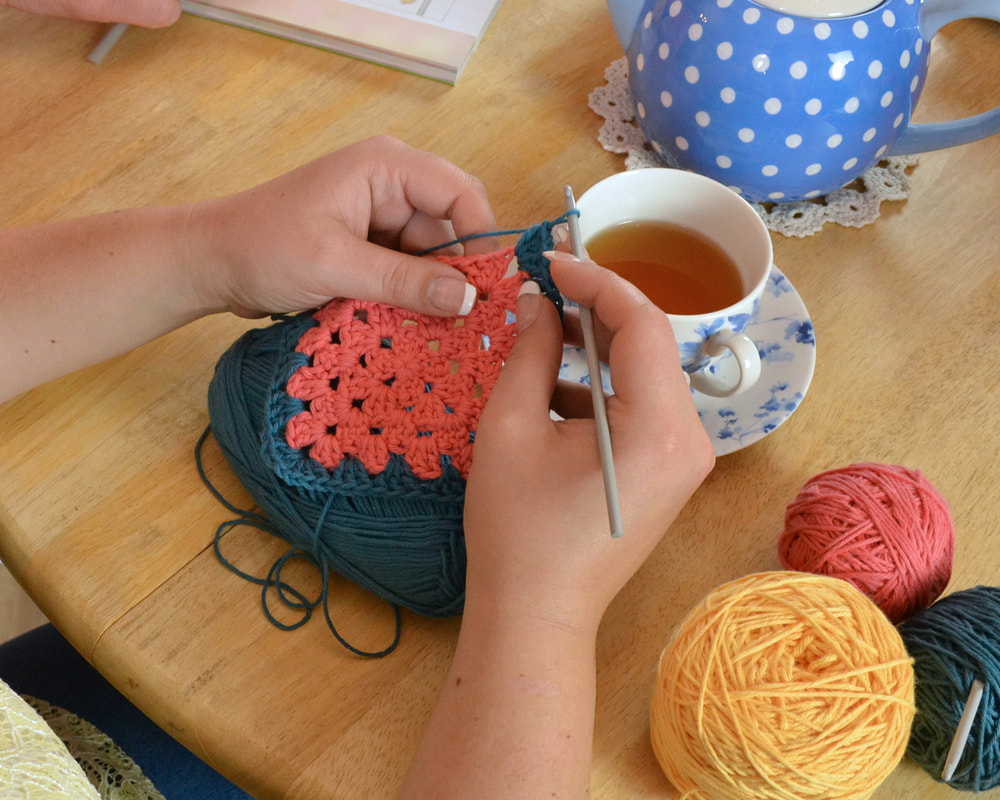 Close up of ladies hands crocheting a granny square at crochet 121 with April Towriess