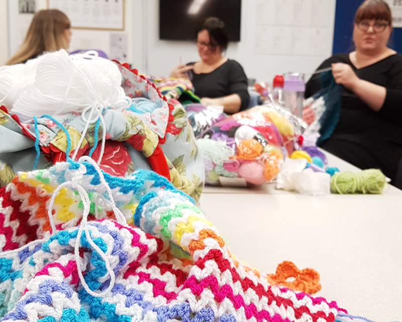 Detailed shot of crochet v stitch blanket with crochet clinic members in the background.