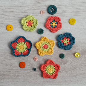 Selection of brightly coloured crochet flowers next to buttons on a grey background