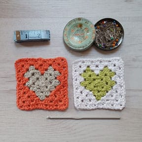 Two crochet granny squares with heart shaped centre next to sewing accessories and crochet hook