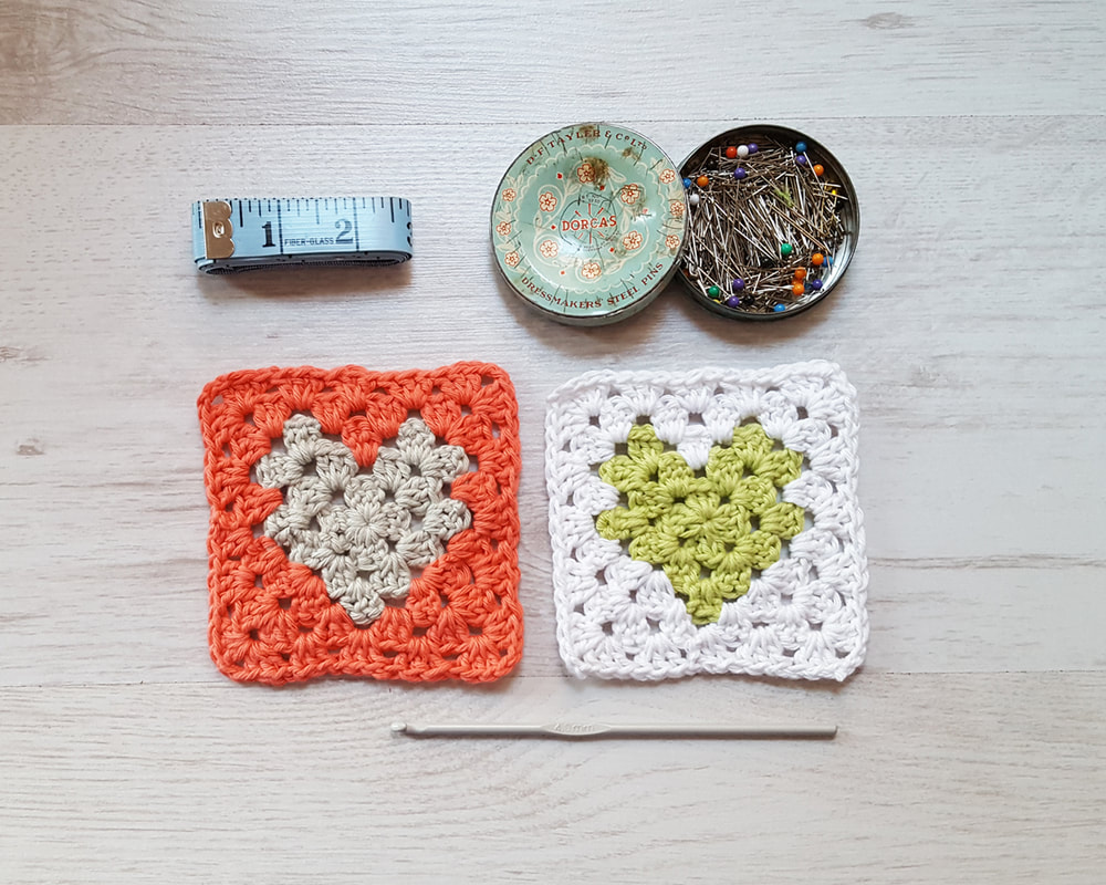Two crochet granny squares with heart shaped centre on grey background surrounded by sewing accessories