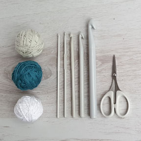 Three cotton yarn balls next to varies sized crochet hooks and sewing scissors on a grey background